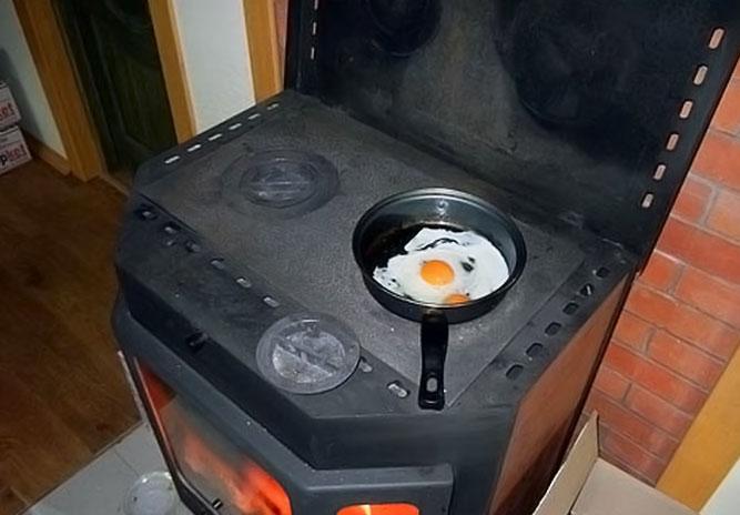 готовка яичницы на съемной конфорке печь-камина Бавария Призматик с плитой